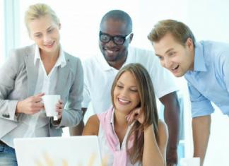 trabajadores riendo frente a un ordenador